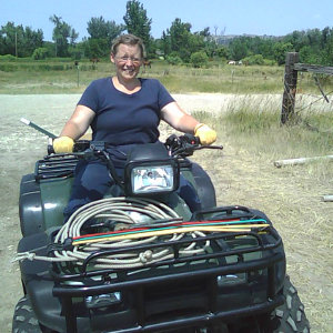 Image: Terri driving an ATV while helping Robert round up stray horses on the ranch in Lodge Grass, Montana.